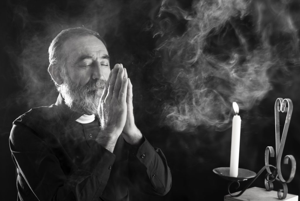 Senior priest praying in dark under candle light